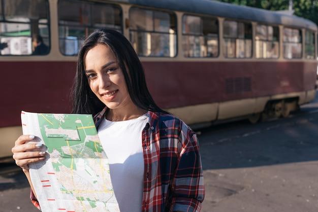 Sorrindo, mulher jovem, olhando câmera, enquanto, segurando, mapa