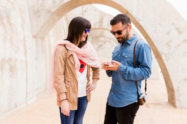 Sorrindo, mulher jovem, olhar, homem, usando, telefone pilha