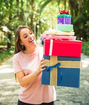 Sorrindo, mulher jovem, olhar, pilha presentes