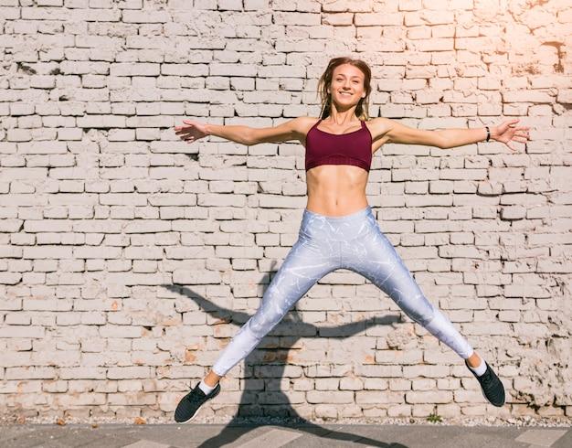 Sorrindo, mulher jovem, pular ar, contra, branca, parede tijolo