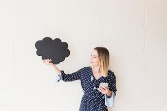 Sorrindo, mulher jovem, segurando telefone móvel, e, nuvem, feito, de, papelão