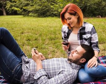 Sorrindo, mulher jovem, segurando, vidro vinho, olhar, homem, usando, telefone móvel, parque