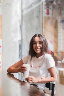 Sorrindo, mulher jovem, sentando, em, a, café, segurando, copo café descartável, em, mão