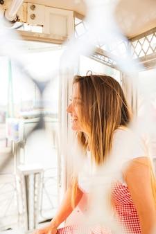 Sorrindo, mulher jovem, sentando, em, a, roda ferris, cabana