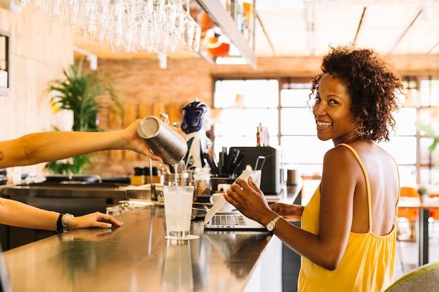 Sorrindo, mulher jovem, sentando, perto, a, barra, contador, e, barman, preparar, coquetel
