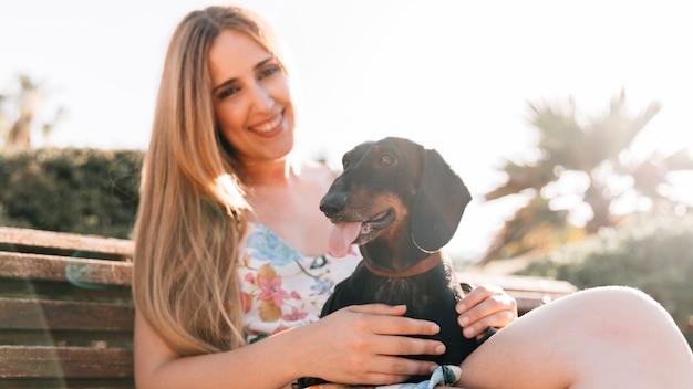Sorrindo, mulher jovem, sentar-se banco, com, dela, cão, furar lingüeta