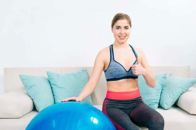 Sorrindo, mulher jovem, sentar sofá, com, pilates, bola, mostrando, polegar cima, sinal