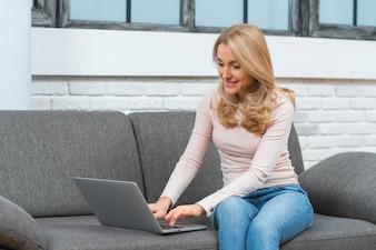 Sorrindo, mulher jovem, sentar sofá, usando computador portátil, casa