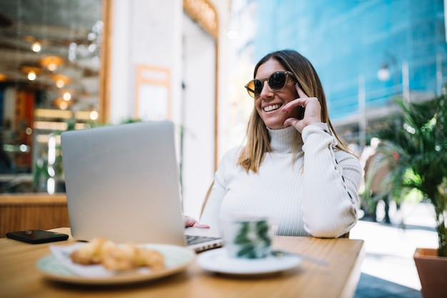 Sorrindo, mulher jovem, usando computador portátil, tabela, com, bebida, e, croissants, em, rua, café