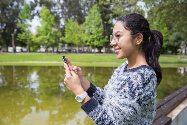 Sorrindo, mulher jovem, usando, smartphone, parque