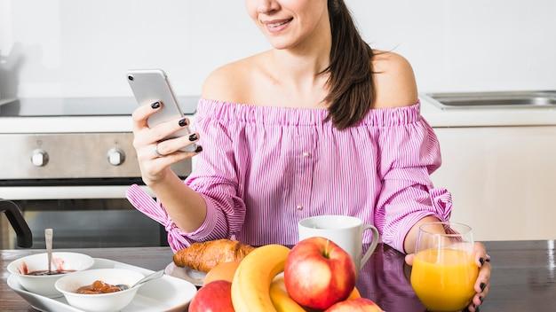 Sorrindo, mulher jovem, usando, telefone móvel, copo segurando, de, suco