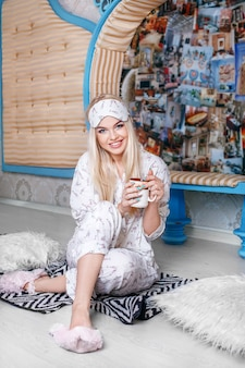 Sorrindo mulher loira sentada no chão de pijama e bebendo