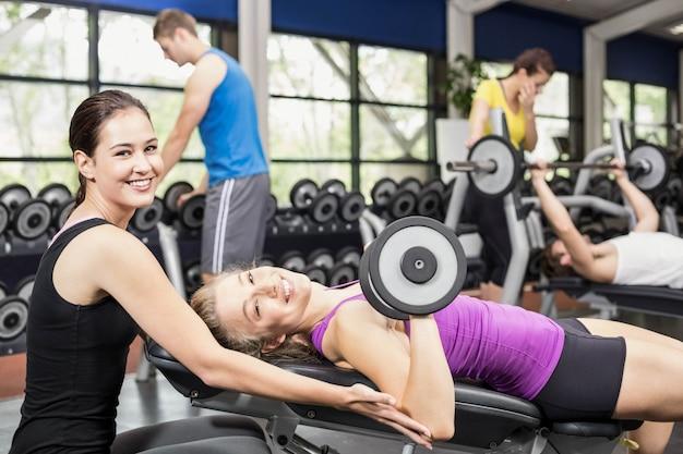 Sorrindo mulher malhando com halteres com treinador feminino no ginásio