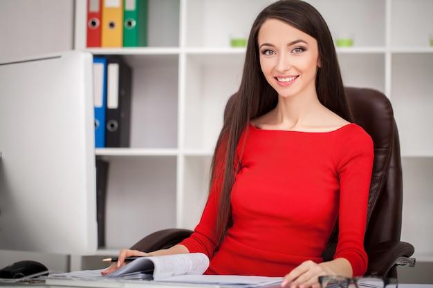 Sorrindo, mulher negócio, em, vestido vermelho, sentando, e, escrita, algo, por, a, tabela, e, olhando câmera