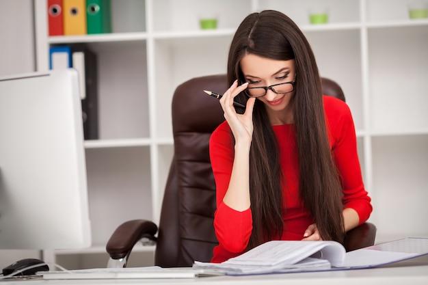 Sorrindo, mulher negócio, em, vestido vermelho, sentando, e, escrita, algo