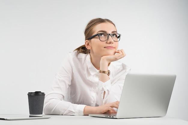 Sorrindo, mulher negócio, sentando, atrás de, um, laptop, com, um, xícara café, e, ipad, tabela, e, olhar, sonhador