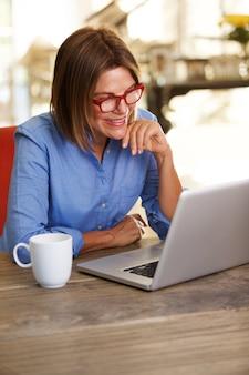 Sorrindo, mulher negócio, sentando escrivaninha, trabalhar, laptop