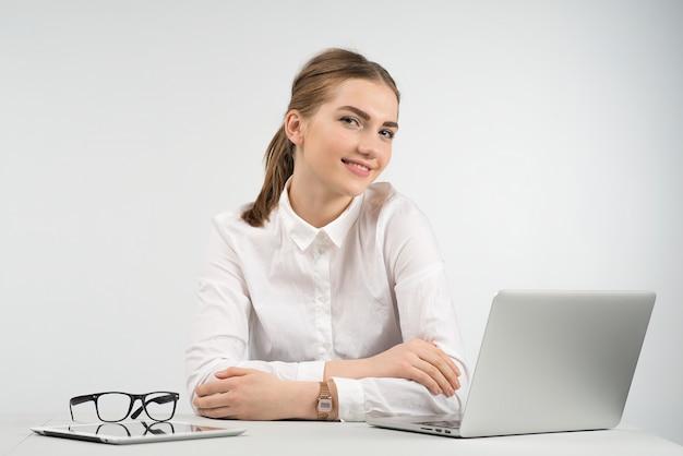 Sorrindo, mulher negócio, sentando, logo, um, laptop, e, olhando câmera