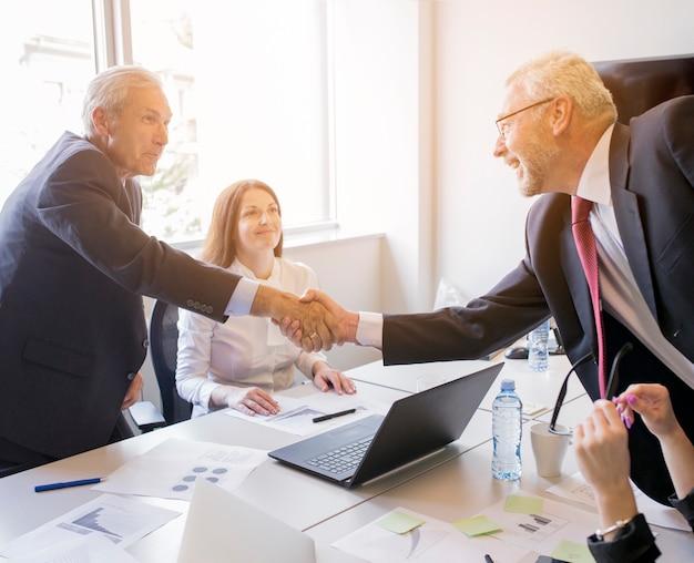 Sorrindo, mulher olha, em, dois, homem negócios sênior, apertar mão