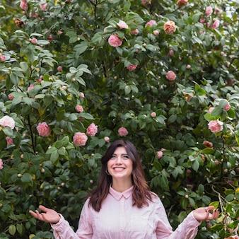 Sorrindo, mulher, perto, flores cor-de-rosa, crescendo, ligado, verde, ramos