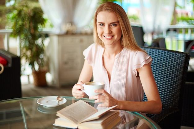 Sorrindo mulher segurando uma xícara de café em suas mãos