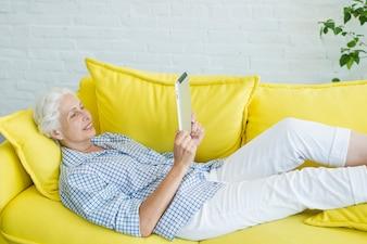 Sorrindo, mulher sênior, mentindo, ligado, sofá amarelo, olhar, tablete digital