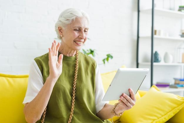 Sorrindo, mulher sênior, olhar, tablete digital, waving, dela, mão