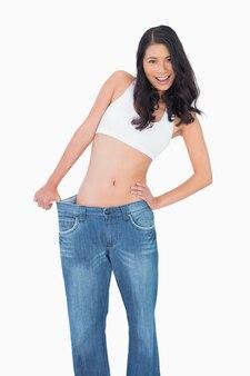 Sorrindo mulher sexy vestindo jeans muito grande