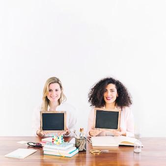 Sorrindo, mulheres, com, blackboards, olhando câmera