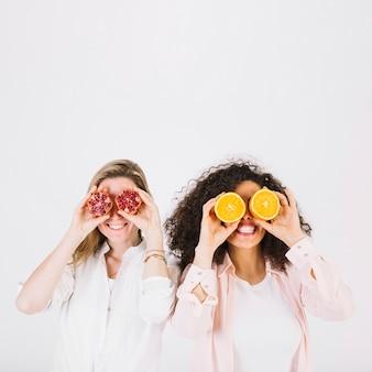 Sorrindo mulheres com romã e laranja