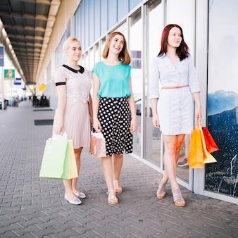 Sorrindo mulheres de pé perto da loja