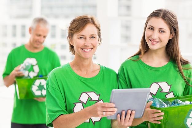 Sorrindo mulheres ecológicas com tablet e caixa de reciclagem