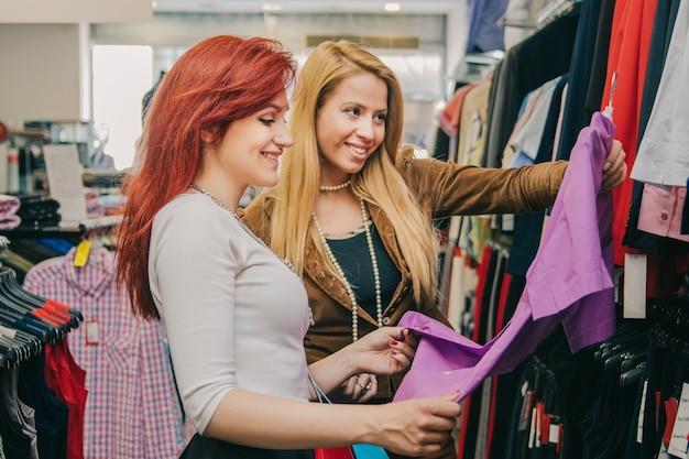 Sorrindo mulheres escolhendo roupas