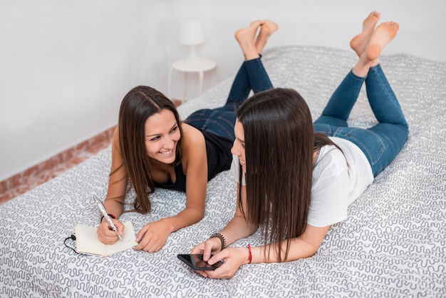 Sorrindo, mulheres jovens, mentindo cama