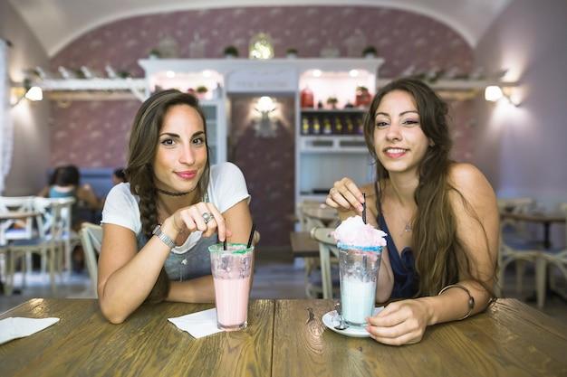 Sorrindo, mulheres jovens, sentando, com, óculos, milkshake