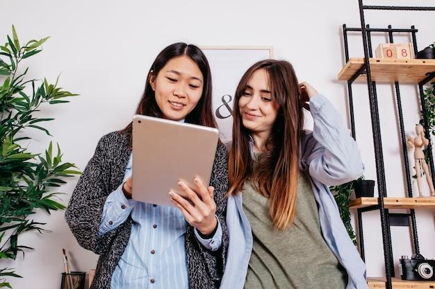 Sorrindo mulheres multiétnica com tablet
