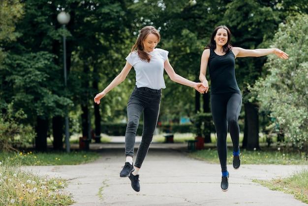 Sorrindo, mulheres, pular, e, segurar passa