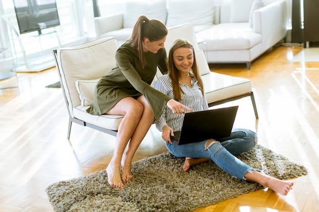 Sorrindo, mulheres, sentar sofá, relaxante, enquanto, navegar, online, shopping, site