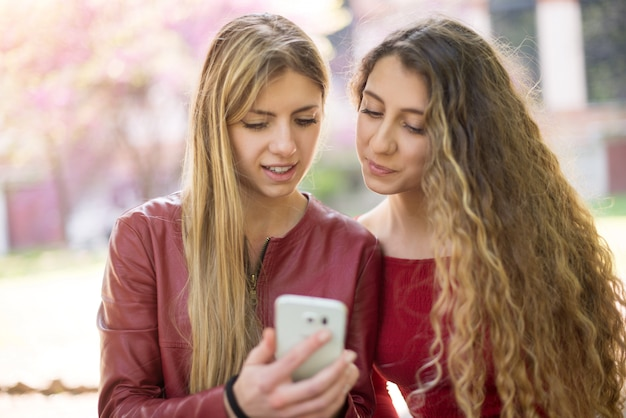 Sorrindo, mulheres, usando, um, telefone pilha