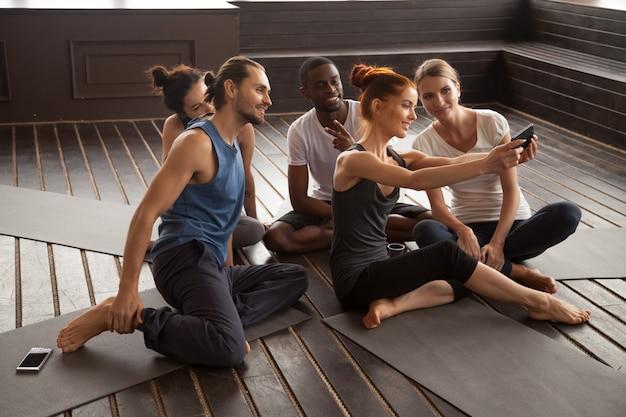Sorrindo multirraciais pessoas fazendo selfie em smartphone no yoga t