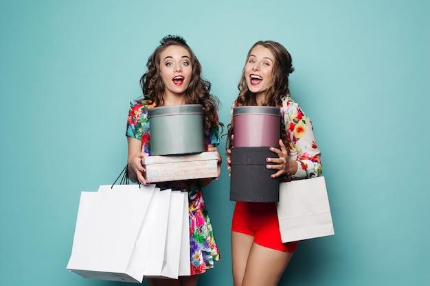 Sorrindo namoradas em roupas coloridas com muitos sacos depois das compras.