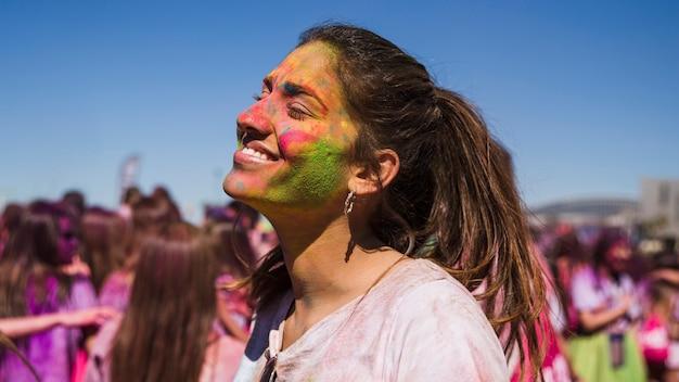 Sorrindo o rosto de mulher jovem pintado com cor holi