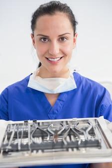 Sorrindo, odontólogo, segurando, bandeja, com, equipamento