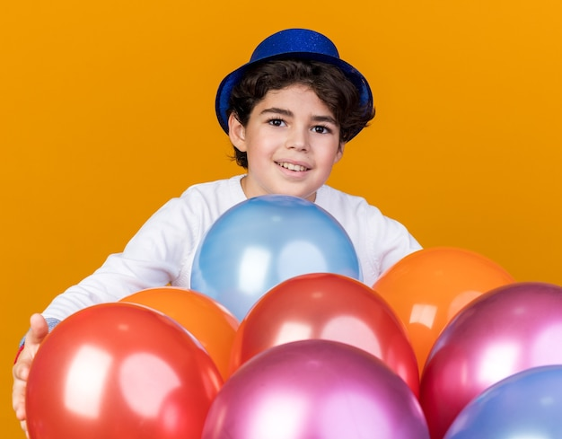 Sorrindo, olhando para a frente o menino com chapéu de festa azul em pé atrás de balões isolados na parede laranja