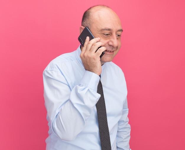 Sorrindo, olhando para baixo, um homem de meia-idade vestindo uma camiseta branca com gravata fala no telefone isolado na parede rosa