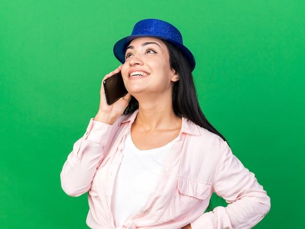 Sorrindo, olhando para cima, uma jovem bonita com chapéu de festa fala no telefone colocando a mão no quadril isolado na parede verde