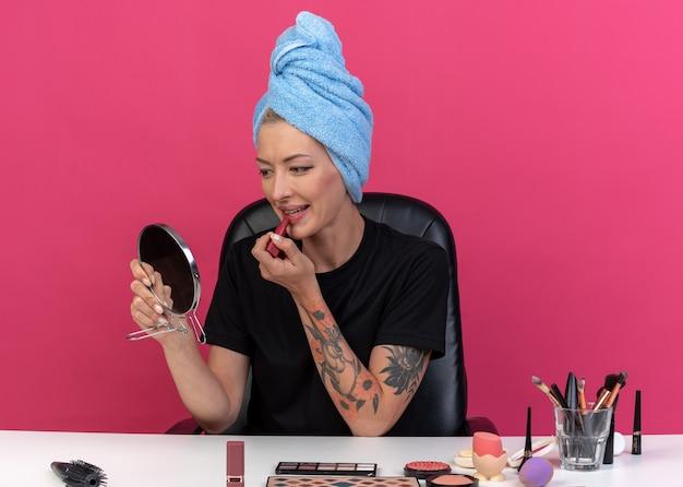 Sorrindo, olhando para o espelho, uma jovem linda se senta à mesa com ferramentas de maquiagem enroladas em uma toalha no cabelo, aplicando batom isolado no fundo rosa