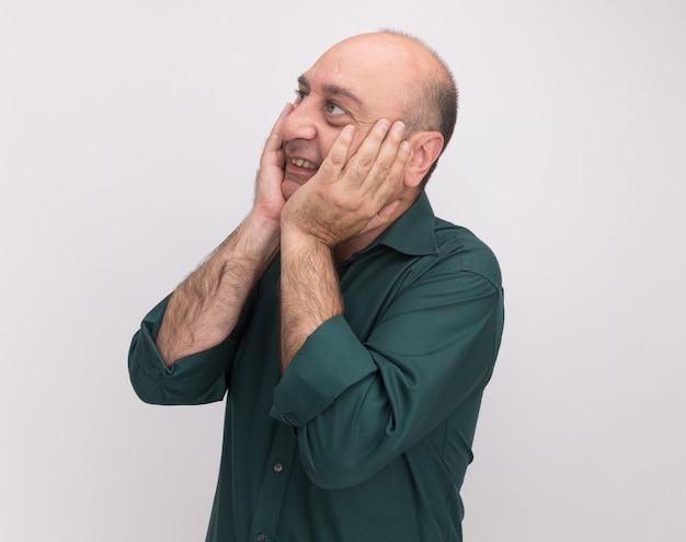 Sorrindo, olhando para o lado de um homem de meia-idade vestindo uma camiseta verde e colocando as mãos nas bochechas isoladas na parede branca