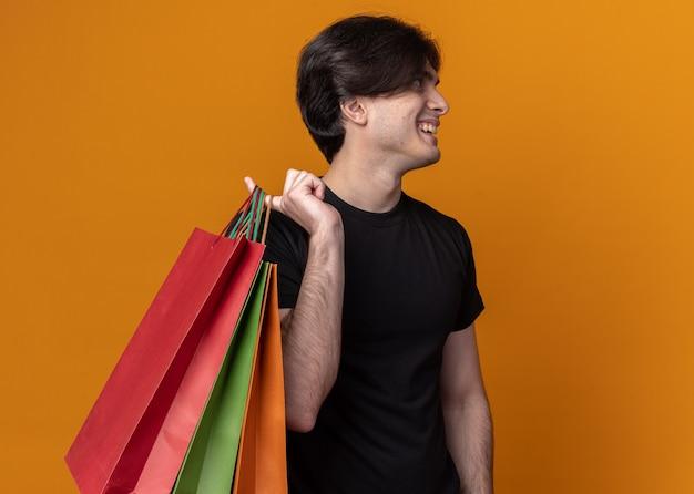 Sorrindo, olhando para o lado jovem bonito vestindo uma camiseta preta segurando uma bolsa no ombro isolada na parede laranja com espaço de cópia