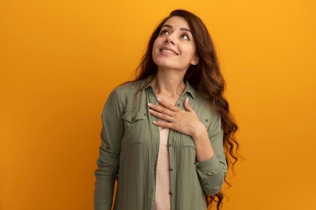 Sorrindo, olhando para uma bela jovem vestindo uma camiseta verde oliva e colocando a mão no coração isolado na parede amarela